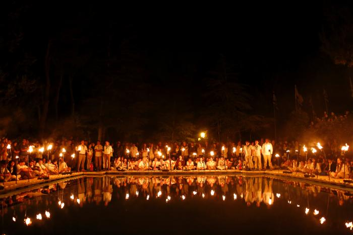 Israeli youth Scouts are reflected in a pool as they light torches, during a memorial ceremony at the Mount Herzl military cemetery, on the eve of Memorial Day in Jerusalem, Israel, 10 May 2016. (Credit: EPA)