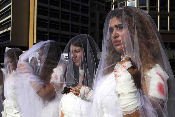 Lebanese women dressed in bloody bridal gowns protest law that allows rapists to avoid prosecution if they marry their victims. AP Photo/Bilal Hussein