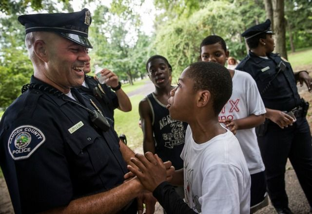 A Camden, New Jersey, police officer talks with a neighborhood child. (Photo: Andrew Burton/Getty Images)