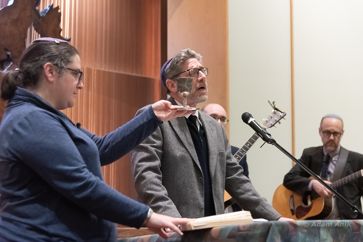 Rabbi Ariann Weitzman holds the cup of wine for Rabbi David Greenstein's prayers at the vigil at B'nai Keshet  to mourn the victims of the Tree of Life massacre Sat. night, Oct. 27.